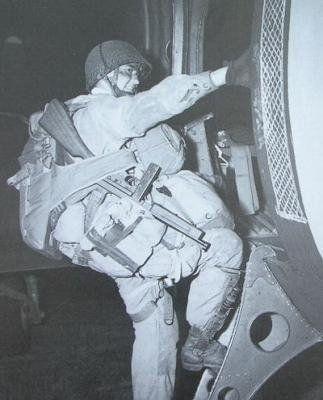 Parachutiste américain, T/4 Joseph F. Gore of 3/506th, lourdement chargé grimpe difficilement l'échelle du C-47 pour se hisser à bord. Pour ne pas perdre sa Thompson pendant le saut l'homme l'a coinçé grâce au bras de fixation de son parachute dorsal. Exeter (England) 5 juin 1944.