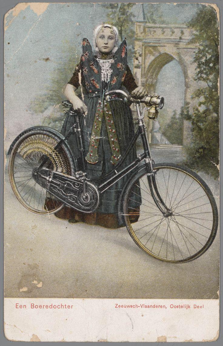 Meisje in Axelse streekdracht met fiets. Het meisje draagt over de ondermuts en het oorijzer een 'trekmuts'. Ze draagt 'dubbele strikken' (dubbele, klaverbladvormige gouden oorijzerhangers) aan de 'krullen' (oorijzeruiteinden) van het oorijzer. Voorop de fiets is een carbidlantaarn bevestigd. 1905-1909 #Axel