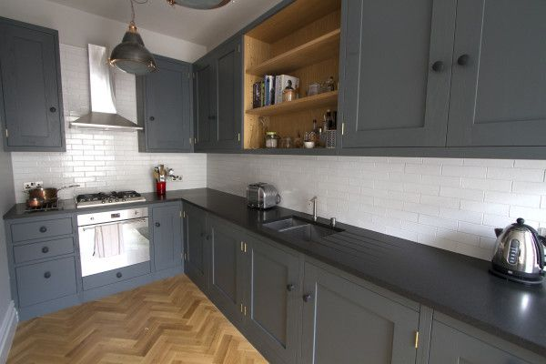 Small oak shaker style kitchen painted in down pipe, parquet flooring, premium black honed granite worktop, and white metro tiles