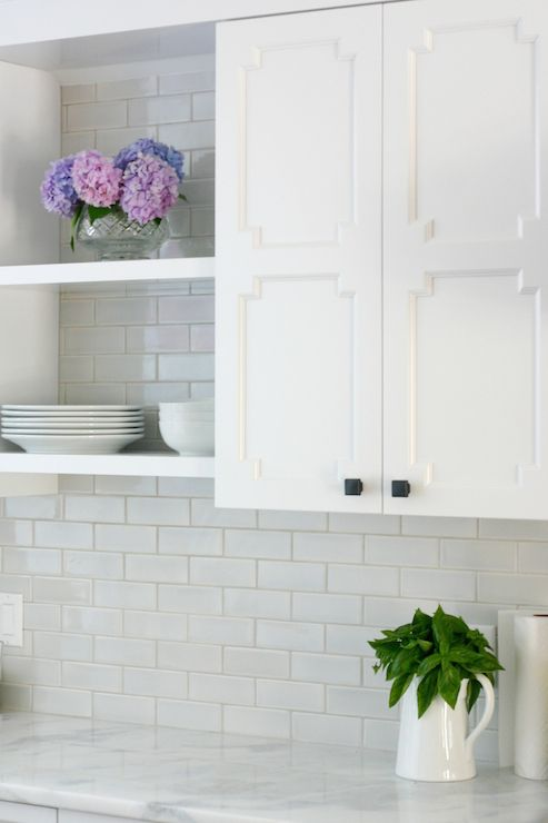 Lovely kitchen features white cabinets with fretwork doors painted Benjamin Moore Decorator's White flanking stacked, floating shelves over Namibian Sky Quartzite countertops paired with Quemere Subway Tile in Ash.