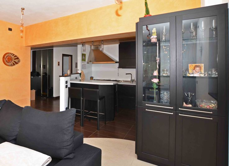 Custom kitchen made of black open pore durmast. It has a doubleface cabinet column: showcase on one side, appliances the other side.