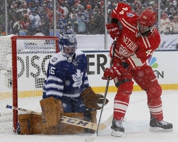 Toronto goalie goalie Jonathan Bernier makes a save on Detroit's Todd Bertuzzi during first period of the Detroit Red Wings and Toronto Maple Leafs game at the 2014 Bridgestone NHL Winter Classic.