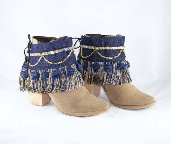 Dress up your boots with these one of a kind and handmade boot covers!  They are unique pieces made from denim fabric, and include the following complements:  - blue and gold fringe - blue cotton pompoms - border - chain  Back lined with denim.  This item fits around boots and is tied in the back with an imitation suede cord. The size is unique and they will fit any boot. They can also be worn on sandals or used as an armlet on the forearm.  The price is for two boot covers, THE BOOTS ARE…