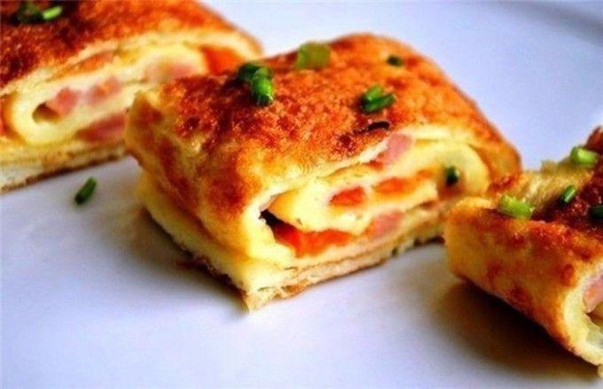 Nejlepší omeleta ke snídani Vajíčka vyšleháme s mlékem. Na každé jedno vajíčko se stále přidává 1 lžíce mléka. Osolíme, opepříme podle chuti a 2/3 hmoty vylijeme na pánev, na které jsme rozpustili 1 lžíci másla. Na vrch navrstvíme na kostičky nakrájenou červenou papriku, šunku, pažitku a nastrouhaný sýr. Necháme chvíli restovat a zalijeme zbylou vaječnou hmotou. Pak pomocí vařečky vajíčkovou placku srolujeme a