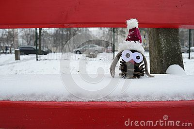 Handmade toy for christmas sits on the snow-clad red bench made from pine cone
