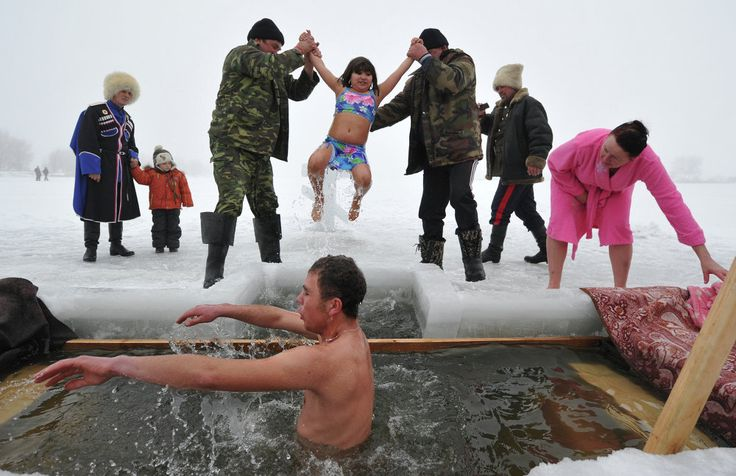 Orthodox faithful dip into the icy waters of a lake during the celebration of the Epiphany holiday near the village of Sretinka, some 40 kms from Bishkek, Kyrgyzstan. January, 19.