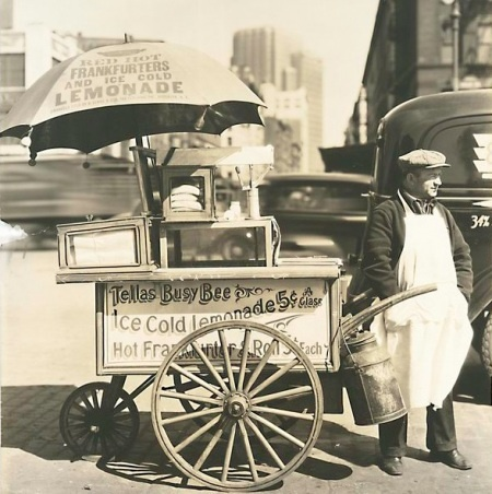 Food vendors in carts. These men used to sell sausage samples on a tooth pick.