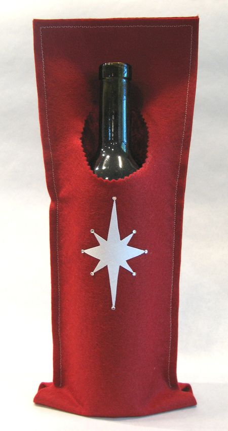 """So I hopped on over to JoAnns and bought a few quarter yard cuts of wool felt.  I bought red, brown and blue felt.  I cut a strip 6"""" x 30"""", cut a circle the diameter of a wine bottle about 3"""" down from one of the short sides (I think next time I will only go down about 2"""").  I folded it and zig-zag stritched around the three open sides, leaving about 1 1/2"""" open along the folded edge (to allow some give for the shape of the bottle)."""