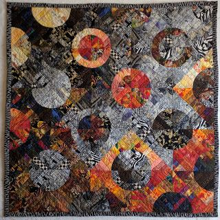 Drunkard's Path quilt variation uses fabric of one-inch strings to add depth. Black, white, grey, brown, and orange.