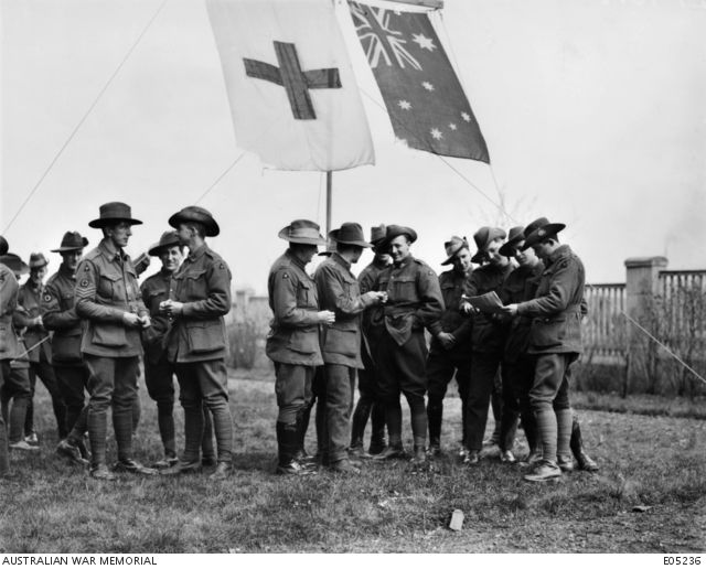 A group of Australian soldiers, mostly members of the 3rd Casualty Clearing Station, gathered near a flag pole at the station.  Both the Red Cross and Australian flag are flying.