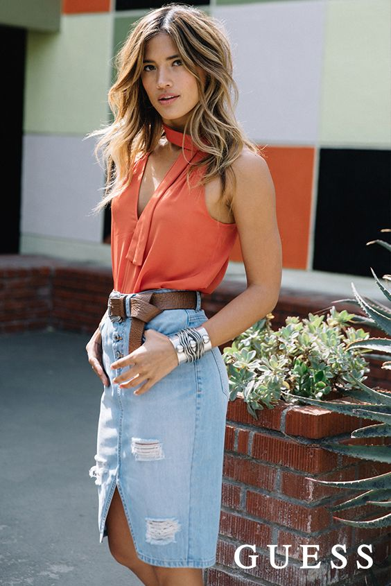 Get LA babe Rocky Barnes' laid back California style with a destroyed high-waisted denim skirt and rust orange blouse. Cinch your waist with a bold leather belt to pull the summer look together! #LoveGUESS