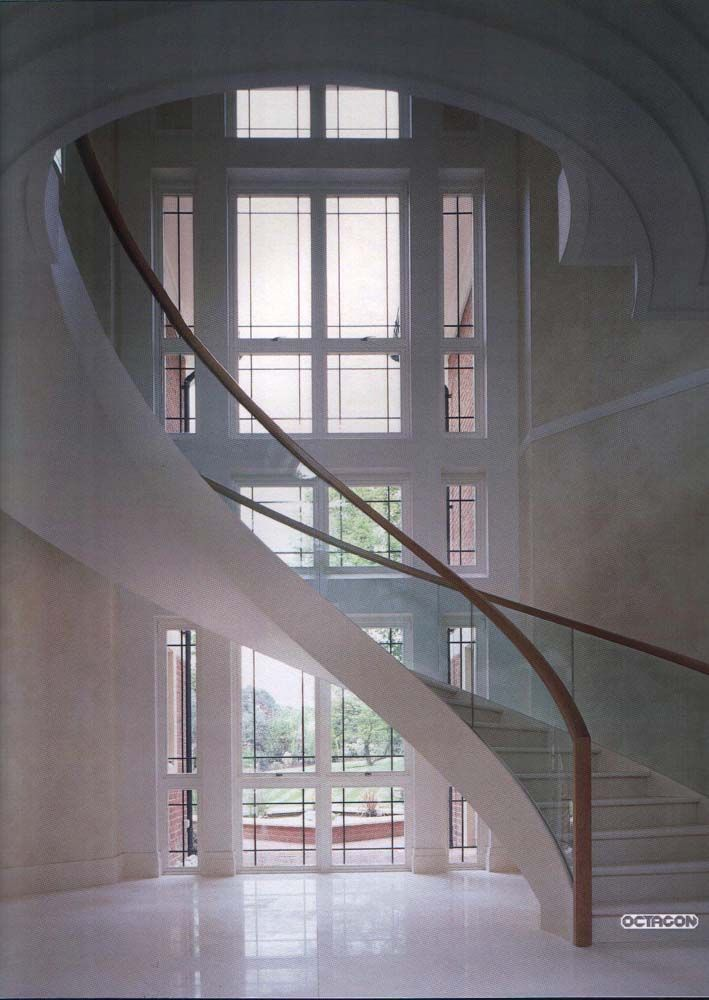 FABRICATED MILD STEEL HELICAL STAIRCASE WITH STRUCTURAL GLASS BALUSTRADE AND WALNUT HANDRAIL.