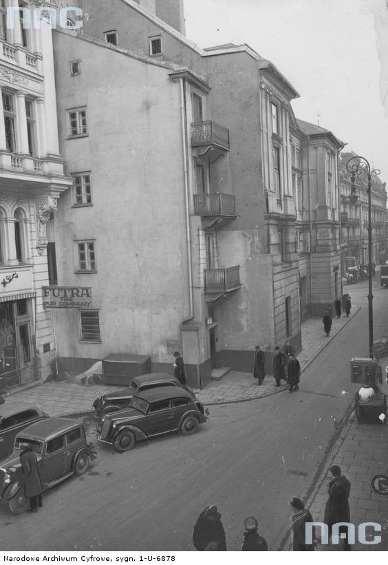Warszawa. Ulica Trębacka. Panorama ulicy. Widoczny sklep z futrami, przed nim samochody.