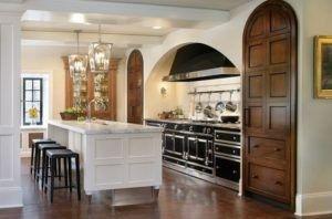 Dies ist eine Inspiration für eine opulente Gourmetküche mit Bögen. Die Bogen gestaltete braune Holztüren sind einheitlich mit der Farbe der Böden. Es gibt auch eine weiße Kücheinsel und drei schwarze Stühle. Die gewölbte Architekturelement, flankiert von Kreis gekrönt Einschub Speisekammer beinhaltet eine La Cornue Range und passende Schränke. Quelle: homesoftherich.net