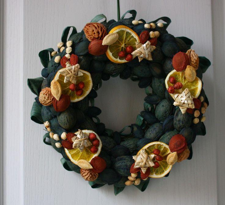 Vítací věnec zelený s pomerančem Ozdobný věnec z tónovaných přírodních materiálů s náznakem přicházejících vánoc. Je vyroben ze skořápek oříšků, pecek, trávy, slámy, sušených pomerančů, pomerančové kůry, šustí, čilimníkového proutí a lýka. Upevněn je na pevném slaměném korpusu. Korpus je obalen batikovým papírem. Ze zadní strany je poutko na ...