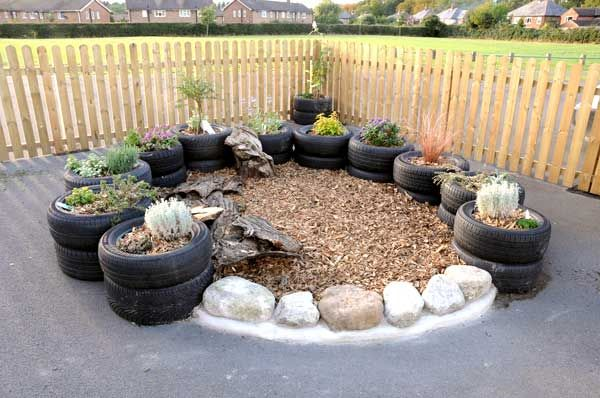 Interesting idea for putting a play area on asphalt, concrete or hard soil in a temporary build.  The tires and rocks can be removed, and the sand and rocks swept up.  Interesting idea for day cares in urban settings without access to grass or soil.