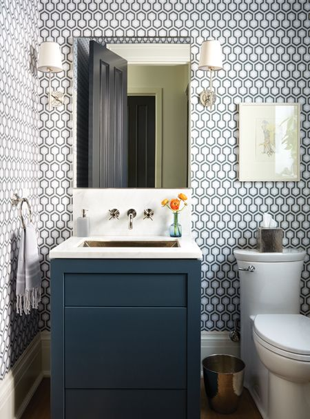 Handsome Powder Room Geometric wallpaper by David Hicks adds bold pattern to this main-floor powder room. Designer Sara Bellamy brought in a tailored navy vanity and simpler fixtures to balance the effect and keep the room from looking too busy.