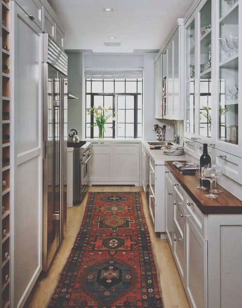 kitchen - wood counters countertops, white cabinets with glass doors over visible shelves, vintage oriental rug runner: