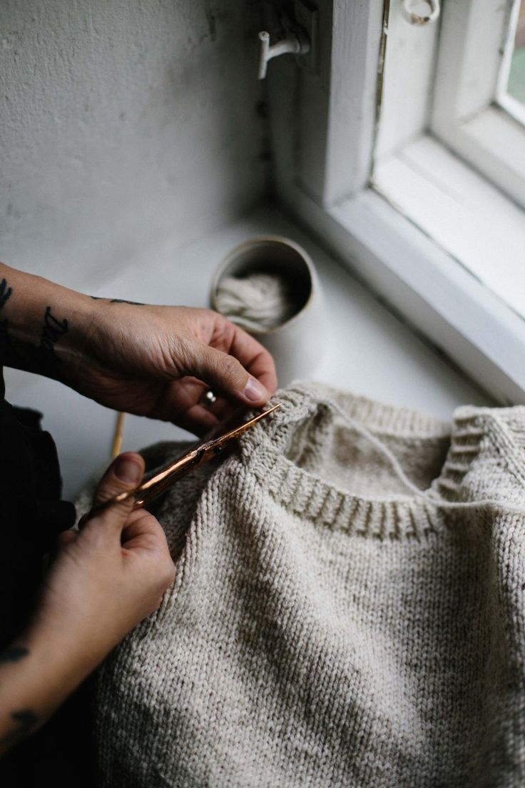 finishing touches on handmade knitted jumper