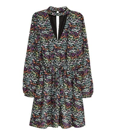 Black/small floral. Knee-length dress in woven fabric. Small stand-up collar, cut-out sections at front and back, long sleeves, and buttons at back of neck