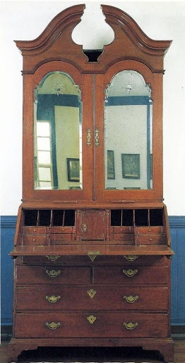 Desk & bookcase, eastern Maryland, 1740-50. Made of walnut, this example has 3 features typical of the late Baroque style in Britain & America: arched door heads, corbeled, or stepped interior drawers, & a well concealed under a sliding cover. Here the well opens to an upper drawer, which, like the lipped fallboard & drawers, reveaals the transitional style of this piece. The beveled & wheel-cut Vauxhall glass of the bookcase was enormously expensive & is therefore rare on American case…