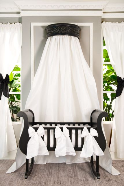 This baby cradle look is oh, so stunning! The beautiful all white cradle bedding, canopy drape with black wall crown and silky crisp white curtains +black bows creates a tailored neutral look for your baby's nursery.  Get all of this and more at brattdecor.com