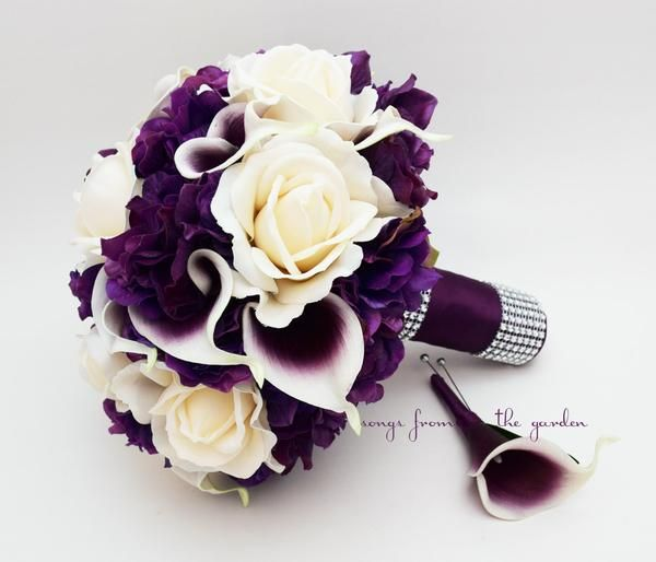 "Ivory Real Touch roses, Picasso mini callas and purple Real Touch hydrangea create a lovely custom real touch flower bridal bouquet that can be yours to have and to hold on your wedding day! I can create it for you as shown or customize it to fit your color scheme. We can work together to create a custom silk flower wedding package for your entire wedding party! This custom silk flower bridal bouquet is 9"" in diameter and includes Picasso (white with purple center) Real Touch mini callas..."