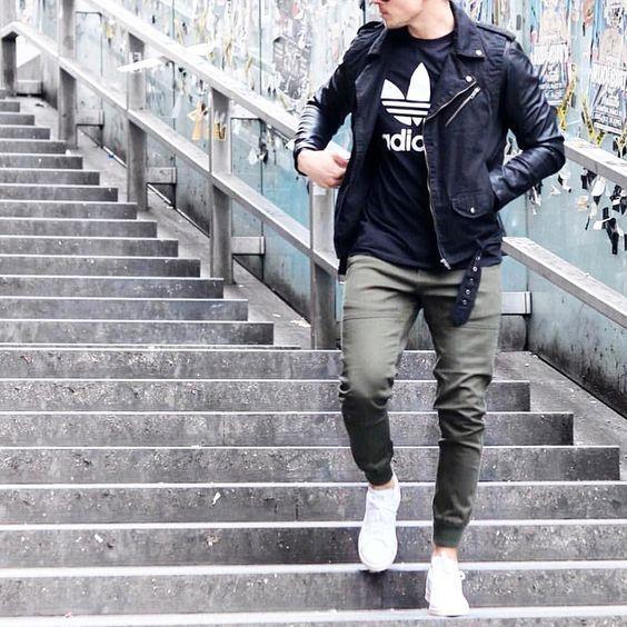 Acheter la tenue sur Lookastic: https://lookastic.fr/mode-homme/tenues/veste-motard-noire-t-shirt-a-col-rond-noir-et-blanc-pantalon-de-jogging-olive/19205 — T-shirt à col rond imprimé noir et blanc — Veste motard en cuir noir — Pantalon de jogging olive — Baskets basses blanches