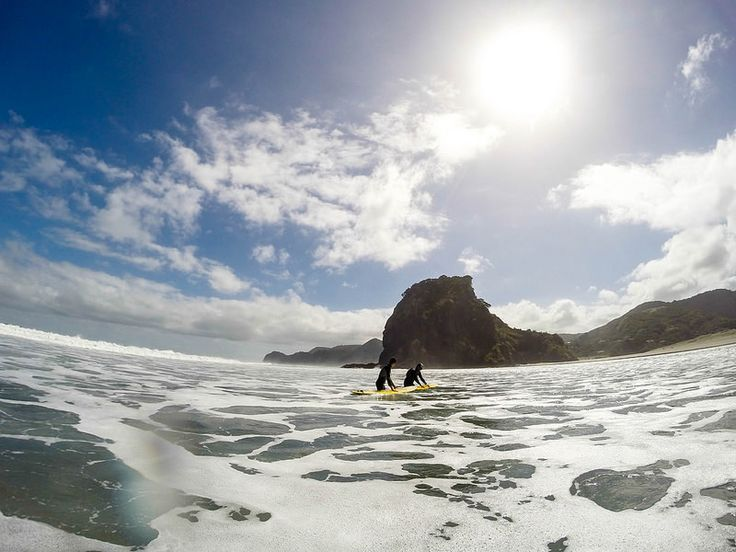 New Zealand - Surfing at Piha. Lion Rock in the back.