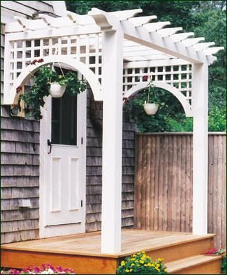 "Entry Pergola - This welcoming entry structure is a charming and dignified extension of your home. Structure includes two 5 1/2"" sq. posts, one 5 1/2"" sq. x 10' carrying beam, 2"" x 4"" cross joists and two 4' x 30"" lattice panels with radius curves. Stained white. Construction of installation methods vary depending on location. Can now be crafted with solid cellular vinyl."