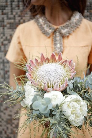 Silver grey, peach and white wedding bouquet of King Protea, blue gum, acacia and peony. Very pretty colours