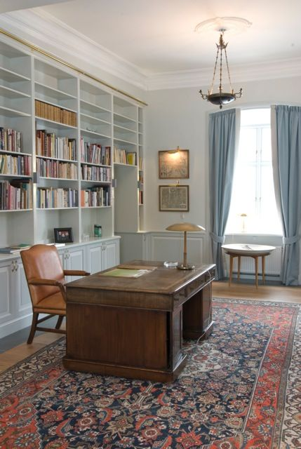 This study has been given an update with a built in bookcase. #AntiqueDesk #BlueCurtains #BookShelves #Bookcase #BuiltInBookcase #BuiltInCupBoard #Desk #GoldDeskLight #GreyScale #GreyWalls #LargeBrownDesk #LeatherDeskChair #PersianRug #PictureLight #Shelves #Study #TrayTable #Vintage