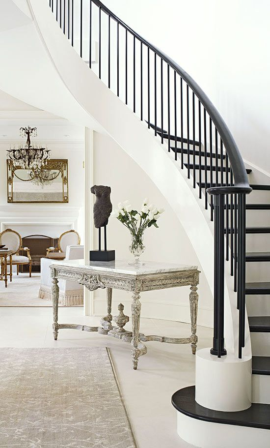 Under the curvy staircase, an antique French table with worn painted wood was updated with a new marble top. A dark banister and steps provide striking contrast. Bright, White, and Inviting Family Home - Traditional Home