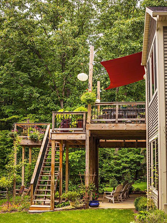The new stepped-down structure shelters a concrete patio and additional seating areas for the homeowners' active, growing family. - Stairs - Deck / Patio / Porch - House Exterior