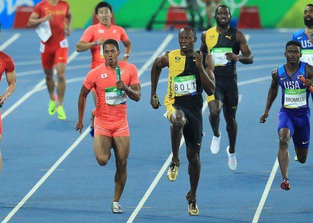 陸上男子400メートルリレー決勝、ジャマイカの最終走者ウサイン・ボルト(手前右)と競り合う日本のケンブリッジ飛鳥(同左)=リオデジャネイロの五輪スタジアムで2016年8月19日、梅村直承撮影