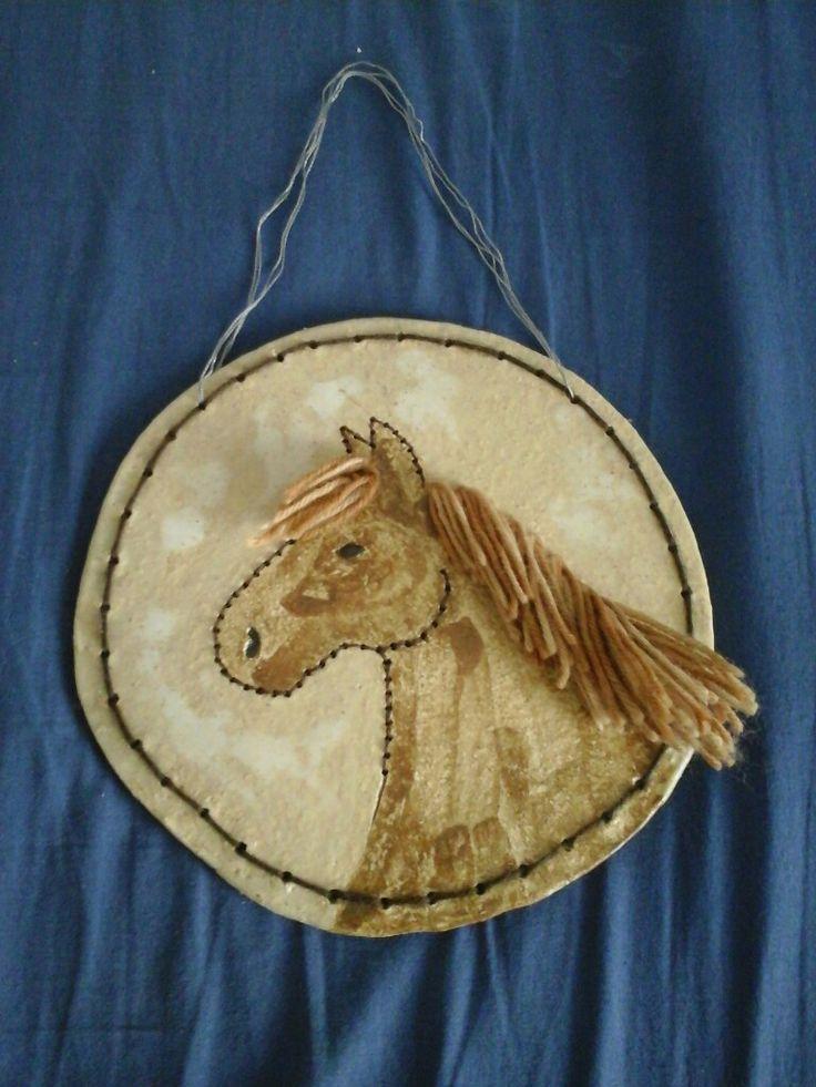 Keramiikassa tehty hevostaulu, johon lisätty lankoja reunaan ja harjaksi. Harja on sienillä värjättyä valkoista 7-veljestä lankaa.