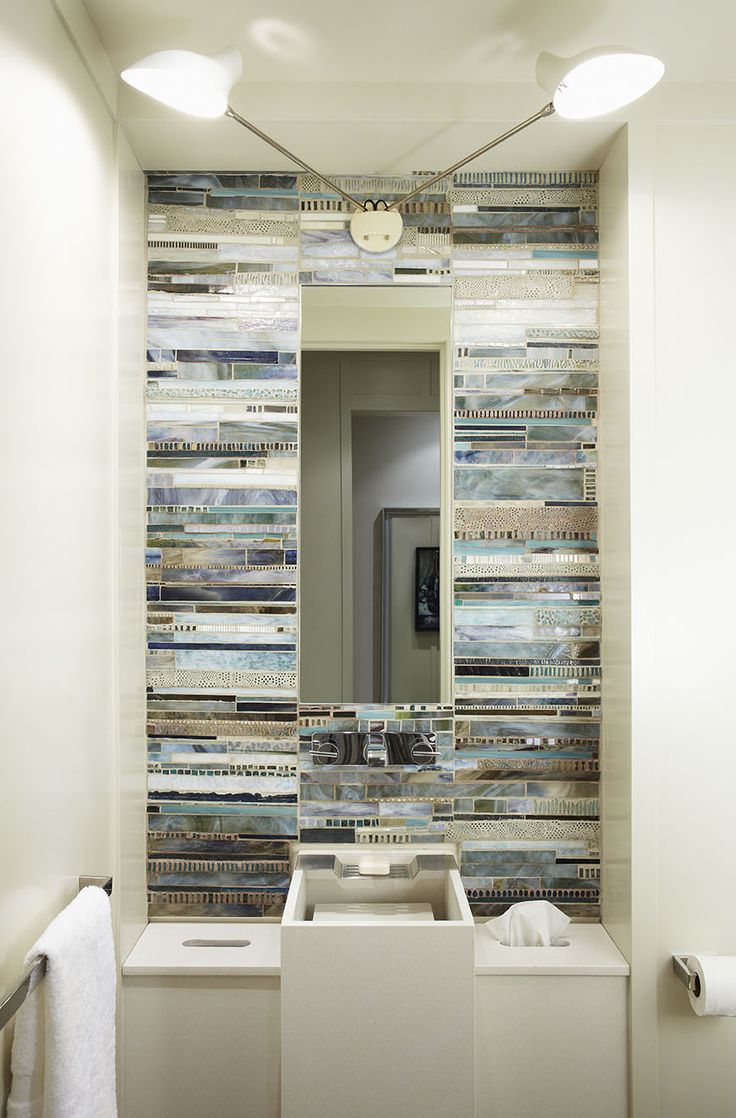 The stone sink, designed with an elevated base, allows water to cascade over the side while concealing the drain. Adjacent cut-outs house tissues and a garbage as well as hidden storage. Artist Nancy Zboch created a stunning mosaic tile wall.  jeffreydouglasdesignEveryday I get to admire the beautiful artistry of Nancy Zboch.   #beauty #nancyzboch #nancyzbochartist #artistry #davidweeks #davidweeksstudio #bespoke #caesarstone #douglasdesignstudio #powderroom #powder #bathroom #design