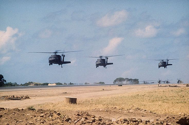 """Three U.S. Army Sikorsky UH-60A Black Hawk helicopters prepare to touch down next to the Point Salines airport runway during """"Operation Urgent Fury"""" on 25 October 1983. The conflict saw the first use of the UH-60 Blackhawk."""