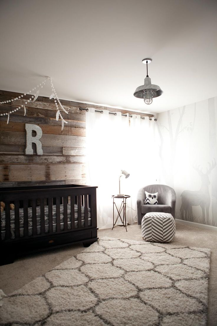 A modern rustic outdoor inspired nursery with a reclaimed wood wall and woodland wall mural.