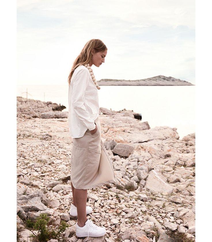 Neutraalkleurige rok met asymmetrisch design. De wikkelrok wordt gesloten met een lus van het lint door een van de drie zilveren oogjes. Combineer met een witte blouse voor een vrouwelijke en modieuze outfit.