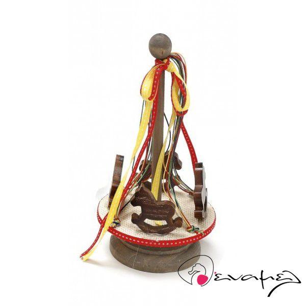 Μπομπονιέρα ξυλινο καρουζέλ με 4 αλογάκια που περιστρέφετε γύρω από τη βάσητου.  Διαστάσεις : 21*13 εκ    Η τιμή αφορά δεμένη έτοιμη μπομπονιέρα με κουφέτα Χατζηγιαννάκης τυλιγμένα σε ζελατίνη ζαχαροπλαστικής - τούλι και κορδέλα σε χρώμα της επιλογής σας.