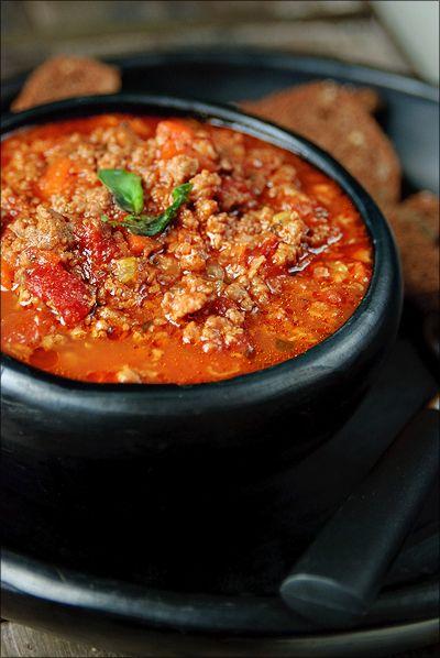 Bereiden: Verhit de boter en de olie in een ovenvaste pot met deksel. Bak hierin het spek op een middelhoog vuur in ca. 4 minuten goudbruin. Voeg de ui, wortel, knoflook en selder toe en laat 5 minuten meebakken. Doe het gehakt erbij en laat meebakken tot het mooi bruin en rul is.
