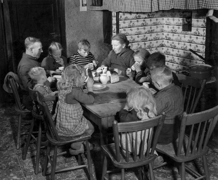 Groot boerengezin met acht kinderen aan het ontbijt voor de schouw in Oirschot, Nederland 3 maart 1950. De familie gaat emigreren.