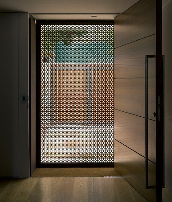 Screen doors can boast plenty of style too. Here, decorative strapwork creates a guarded but attractive boundary between the front door and the street outside. Fresh air filters right through to cool the home, but the hot sun doesn't get very far.