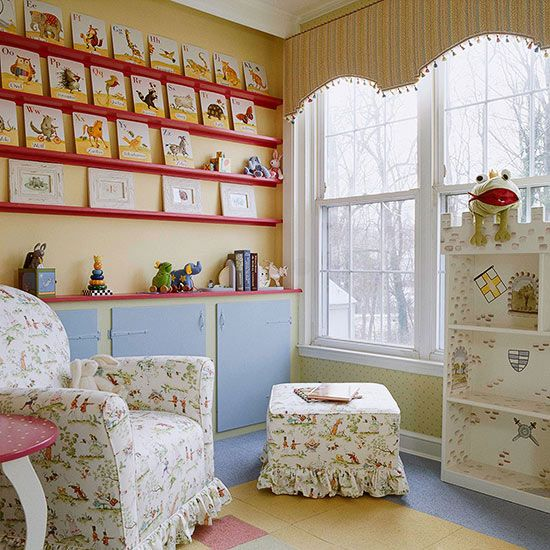 A wall of floating shelves offers oodles of display space in this whimsical nursery. The shelves were painted red to pick up on accent colors used in the fabrics throughout the room. Right now the shelves house alphabet cards, but those can easily be switched out as baby grows.