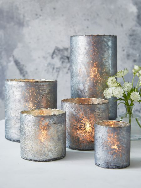 This collection of antique silver hurricanes is perfect for adding some soft lighting to your home.