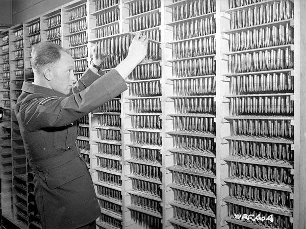 An unidentified corporal examining ammunition, No. 1 Bombing and Gunnery School, RCAF, Jarvis, Ontario, 1941 / Un caporal inconnu examine des munitions à la 1re École de bombardement et de tir de l'ARC à Jarvis (Ontario), en 1941 | by BiblioArchives / LibraryArchives