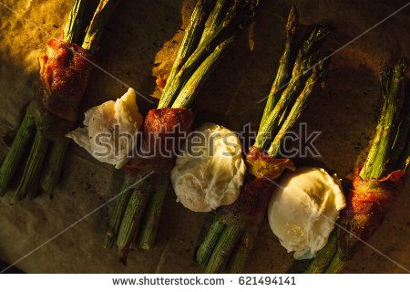 Roasted green asparagus wrapped in Spanish ham and poached eggs in the sun.