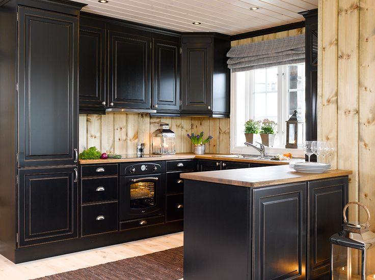 Et flott kjøkken i heltre, malt i Antikk svart. Dørene har klassiske ramtre fyllinger og benkeplaten er levert i brunpatinert/oljet eik. Knottene på dørene og skålhåndtakene på skuffene er i antikk…