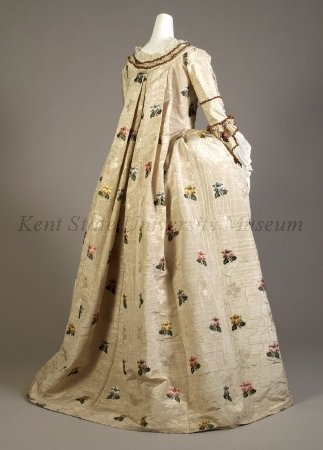 Dress 1748-1752. Petticoat, stomacher of white moire brocaded with red, purple, yellow and blue sprays. Hem ruffle, trimmed with chenille, matching stomacher: Separate pocket on a string with matching fabric.